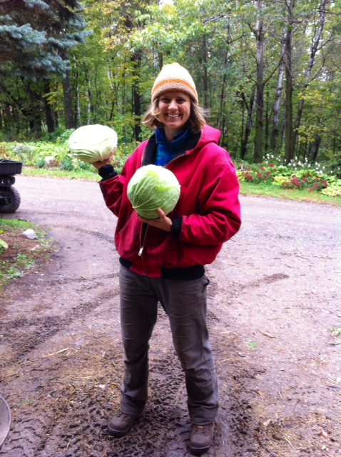 smiling woman holding two cabbages