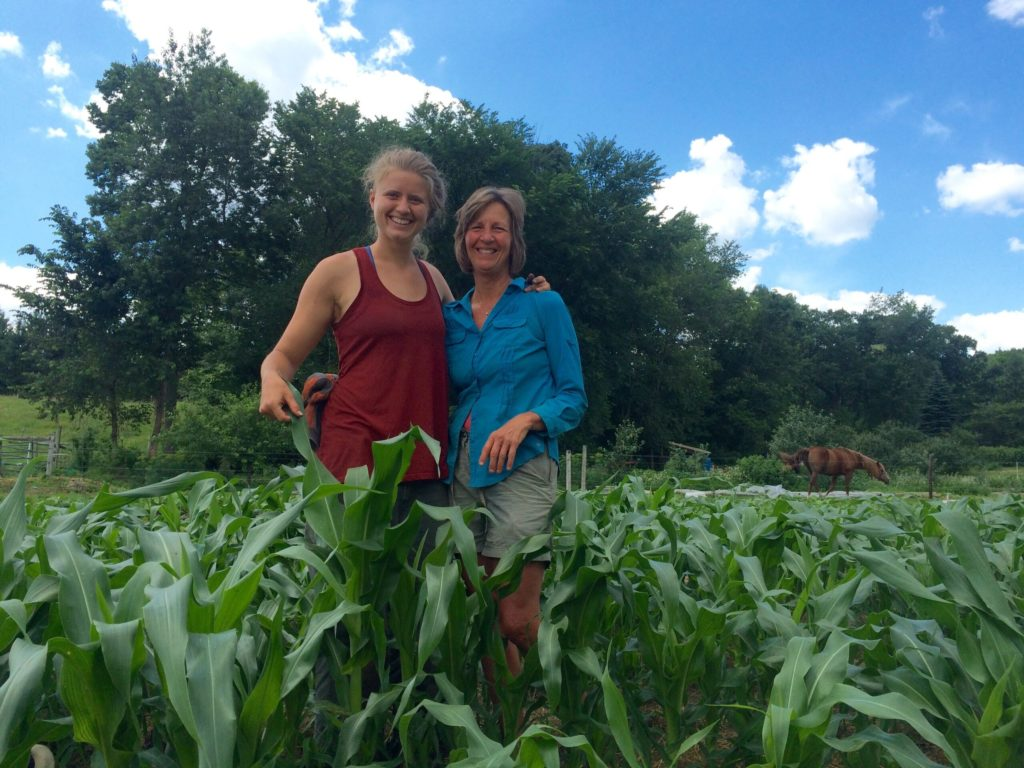 two women smiling in a field of corn